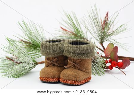 Mini felt boots and pine covered with snow flakes