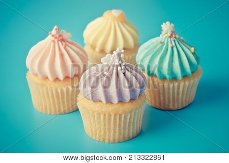 Four colorful cupcake on blueish background in vintage pastel tone