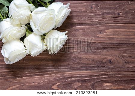 Macro view of beautiful white roses bouquet on the corner of the wooden table. Romantic wallpaper for beloved couples.