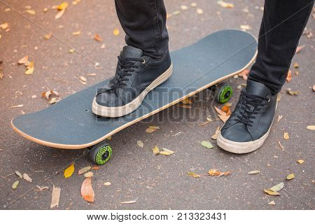 Close-up of a skateboarder's foot in black krosovkah on a skateboard, among the autumn leaves, the right foot of a skateboarder stands on a skateboard. The concept of sport.