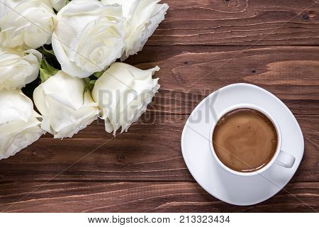 Romantic white bouquet of white roses with cup of coffee on the wooden table.