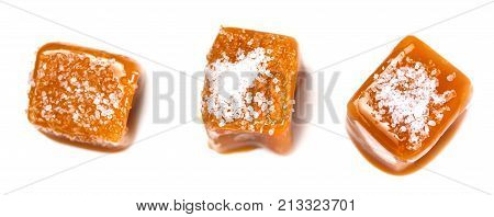 Salted caramel pieces and sea salt isolated on white background. Golden Butterscotch toffee caramels. Toffees macro.