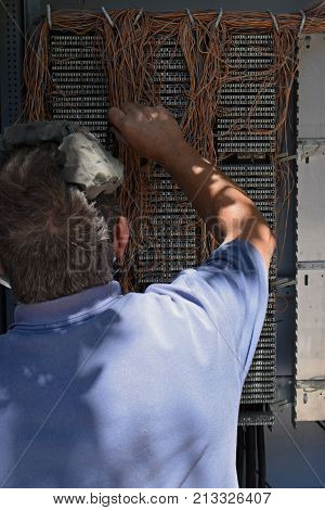 ATHENS GREECE - AUGUST 1 2017: Engineer working on telephone wiring junction box switchboard.