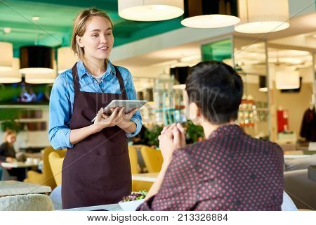 Portrait of smiling young waitress taking order from client in cafe using digital tablet, copy space
