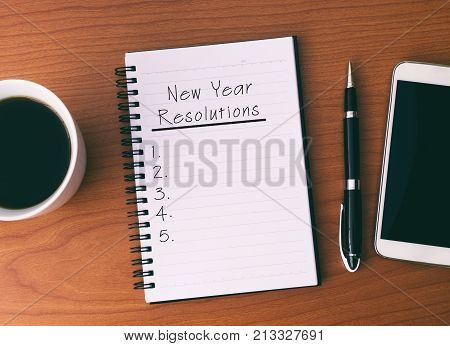 New Year's Resolution List On Notepad, Background Coffee, Pen And Smart Phone.