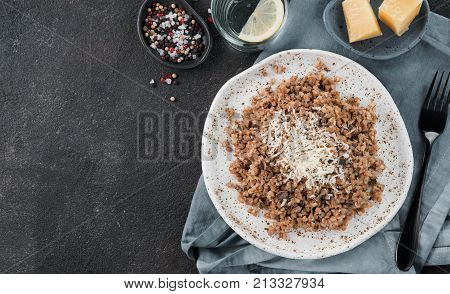 Buckwheat risotto with dried mushrooms served parmesan cheese in craft plate on black cement background. Gluten-free and vegetarian buckwheat recipe ideas. Copy space. Top view or flat-lay.