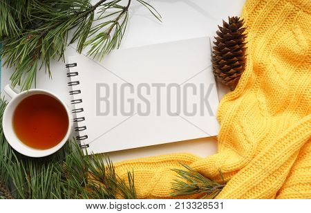 Christmas background with a Cup of tea, a notebook, fir cones, branches of pine with large needles and a yellow sweater. Top view, close-up