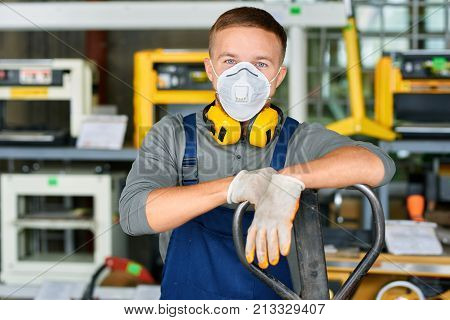 Portrait of cheerful young worker wearing protective mask posing looking at camera and enjoying work at modern factory