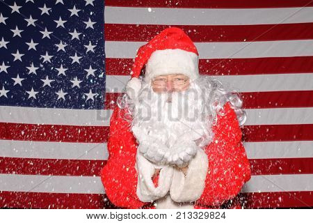 Santa Claus stands in front of the American Flag. Santa Claus Blows Snow or Glitter from his hands while in front of an American Flag.