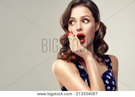 Shocked and surprised girl screaming and  looking to the side presenting  your product . Curly hair woman amazed .Beautiful girl  with curly hair and red nails manicure . Expressive facial expressions