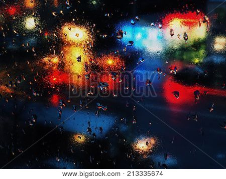 Autumn rain leaves abstract rain drops on a window glass. Background with blurred car and traffic lights. Colored lighting.