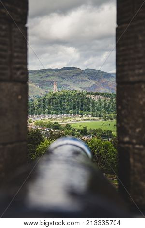 The National Wallace Monument viewed through one of the canon embrasures at Stirling Castle Scotland