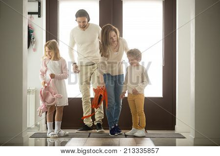 Children siblings returning sweet home with parents, happy family of four coming back to house after walking together from school or work, father mother and two kids son daughter standing in hall