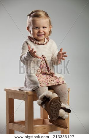 eager little girl is sitting on a chair on grey background