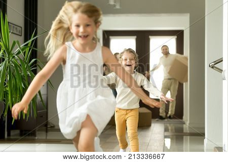 Excited children running on camera, funny little girl and boy having fun playing happy to move in new own big modern house, young family with kids and cardboard boxes entering home at moving day