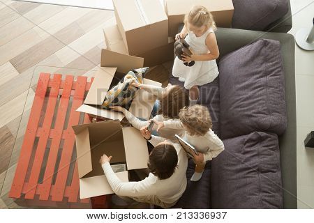 Kids helping parents to unpack boxes on sofa in cozy living room, happy young family with children having fun in new home together sitting on couch, moving into house relocation, top view from above