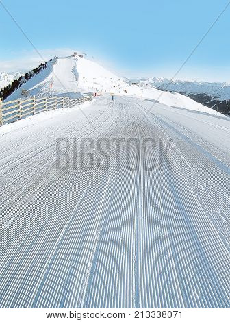 Newly groomed snow on ski slope at ski resort, skiers and mountain peaks