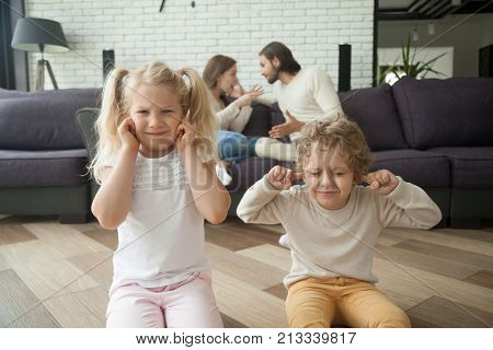 Little children boy and girl put fingers in ears not to hear parents arguing at background, son and daughter tired of family conflicts, parental arguments impact on children, divorce and kids concept