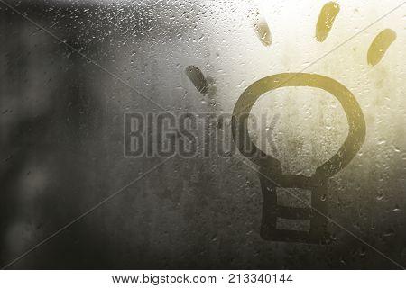 drawing a light bulb on the sweaty glass symbolizing a new idea