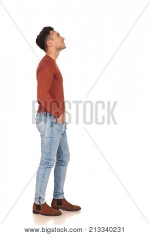 casual young man standing in line is looking up at something on white background