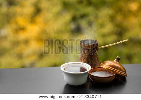 Hot tasty steaming coffee brewed in traditional turkish coffee pot and sugar, cafe outdoors, autumn background