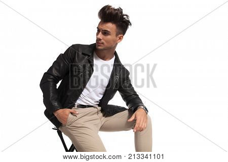 fashion man sitting and looking back over his shoulder on white background