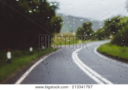 Rainy day driving on a single carriageway in slippery conditions blurred out of focus