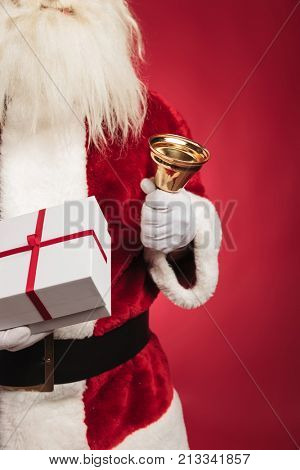 cutout image of santa claus holding present and ringing bell on red background
