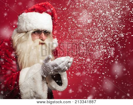 santa claus is blowing snow flakes out of his palms on red background