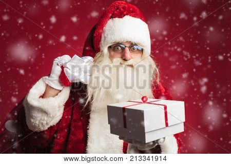 santa claus holding bag on shoulder and offering a gift box on red background with snow flakes