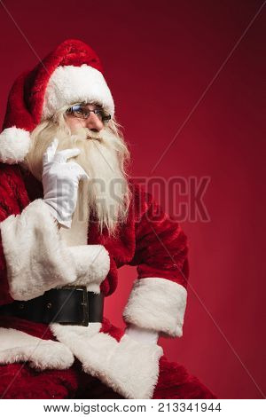 cutout image of a thoughtful santa claus sitting on a chair on red background