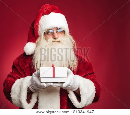side view of santa claus holding a present box on red background