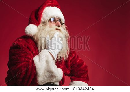 pensive santa claus touching beard and chin and looks to side on red background