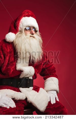 cutout side image of santa claus sitting on a chair looking away from the camera