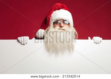 santa claus on top of a big blank billboard on red background