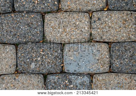 Detail Of Ground Bricks With Dried Leaves In Cracks