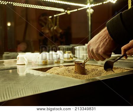 Close up hands of a man cooking turkish coffee on hot golden sand. Soft focus