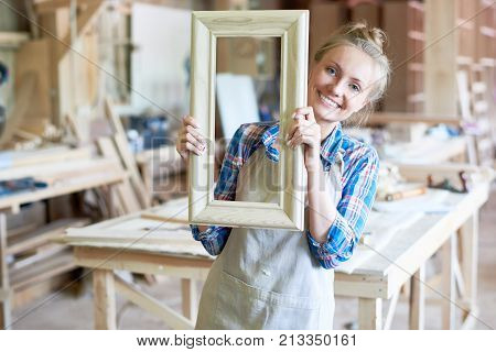 Portrait of happy young woman wearing apron smiling to camera holding wooden frame in modern joinery shop