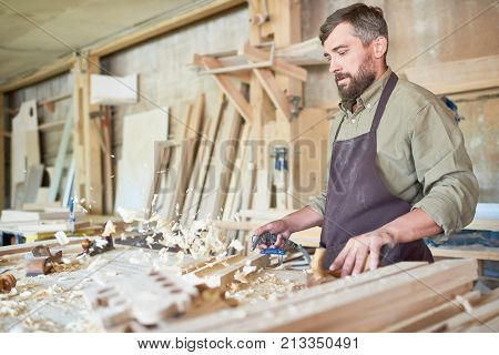 Portrait of mature bearded carpenter making furniture in modern workshop, blowing off wood shavings from workstation, copy space