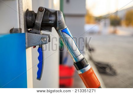 Fuel pistol close up at the gas station, abstract car background