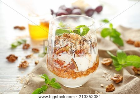 Delicious parfait with walnut and oatmeal in glass on table