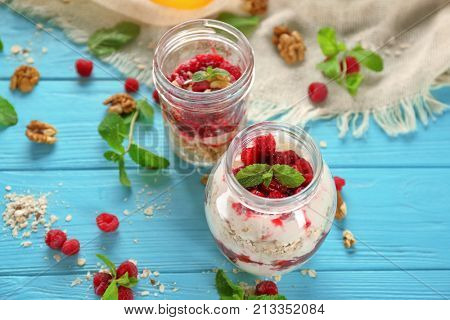 Delicious parfait with raspberry and oatmeal in glass jars on table