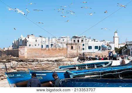 Essaouira, Morocco - March 27, 2008: Blue Blue Fishing boats and seagull in front of Essaouira ramparts - Morocco. Until the 1960s Essaouira was generally known by its Portuguese name Mogador.