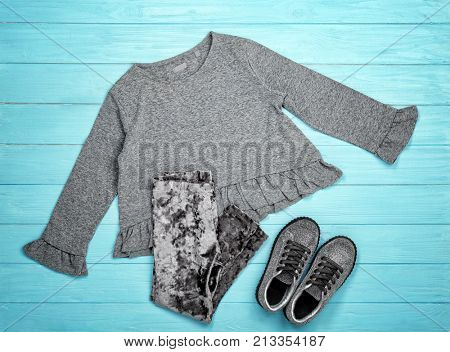 Set of child's clothes on wooden background