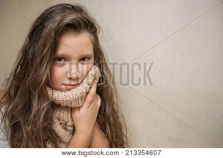 little sick girl with tousled hair in a warm knitted sweater. a sore throat. a sore tooth. girl is sick with the flu or a cold. place for text.