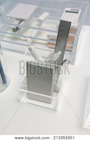 Square shape clear acrylic holder for stationery organizer on white office table against blurred background.