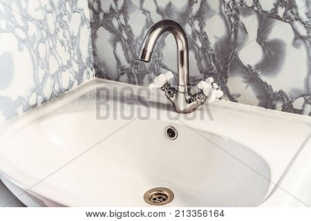 Chromed silvery washbasin with bright white sink and two valves