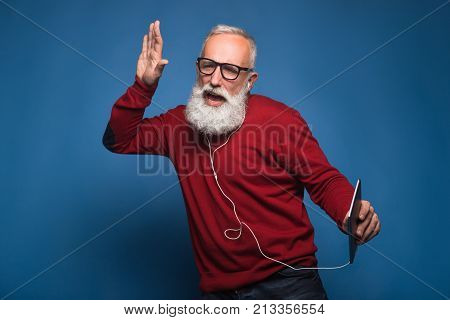 Expectation from a new song. Happy modern bearded man listening a new music from tablet. Man with headphones listen to music isolated on blue background. Happily dances from cool music on headphones.