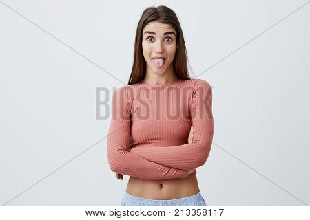 Close up portrait of charming good-looking joyful caucasian woman with long dark har in casual stylish clothes crossing hands, showing tongue in camera with raised eyebrows and funny face expression