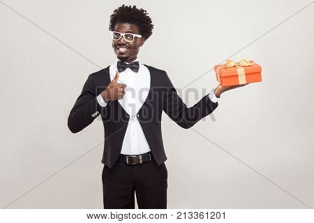 African Man Thumbs Up And Holding Gift Box.